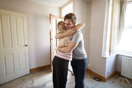 Excited Young Couple Hugging By Front Door Of New Home