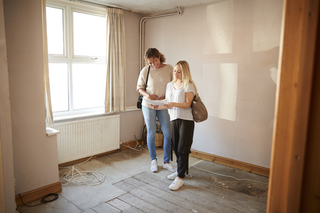 Two Female Friends Buying House For First Time Looking At House Survey In Room To Be Renovated