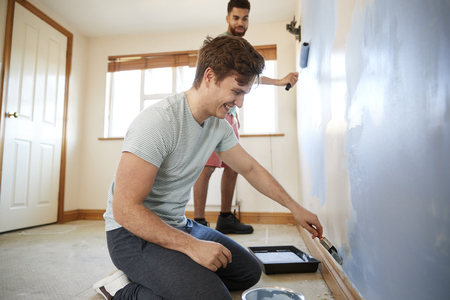 Two Men Decorating Room In New Home Painting Wall Together Banque d'images - 113940587