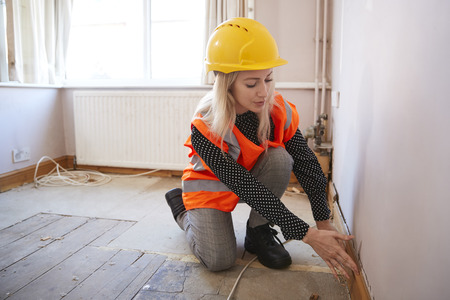 Female Surveyor In Hard Hat And High Visibility Jacket Carrying Out House Inspection Stock Photo