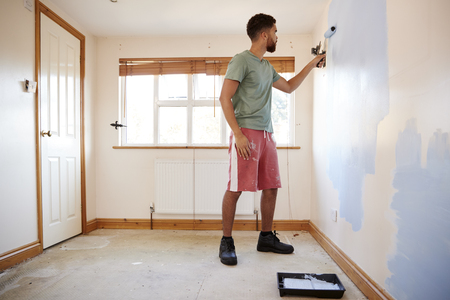 Man Decorating Room In New Home Painting Wall Banque d'images - 113940591