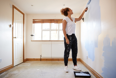 Woman Decorating Room In New Home Painting Wall Banque d'images - 113940592