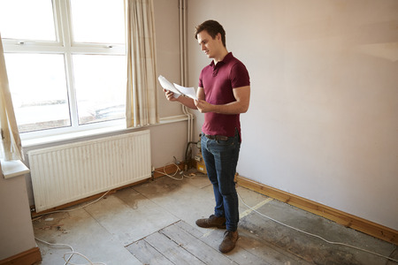 Male First Time Buyer Looking At House Survey In Room To Be Renovated