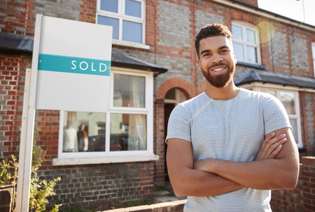 Portrait Of Excited Man Standing Outside New Home With Sold Sign