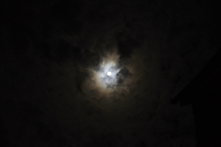 Full Moon Appearing Through Clouds At Night