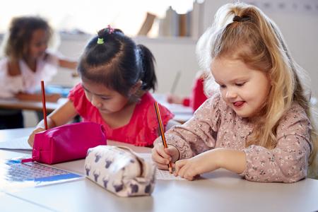 Zwei junge Schulmädchen sitzen an einem Schreibtisch in einem Kindergarten-Klassenzimmer arbeiten, Nahaufnahme