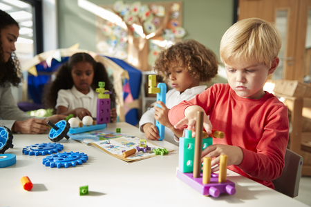 Infant school boy sitting at a table using educational construction toys with his classmates, close up