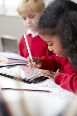 Close up of a schoolgirl sitting at desk next to a boy in an infant school classroom, using a tablet computer and stylus, selective focus, vertical