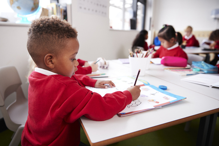 Young black schoolboy wearing school uniform sitting at a desk in an infant school classroom drawing, close up, side view Imagens