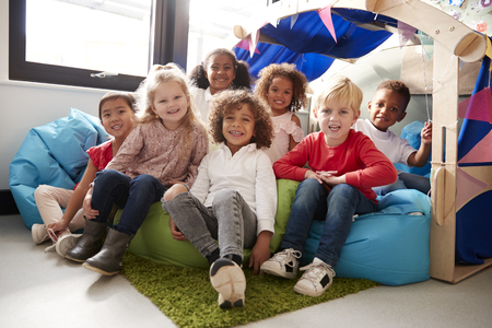 A multi-ethnic group of infant school children sitting on bean bags in a comfortable corner of the classroom, smiling to camera, low angle, close up