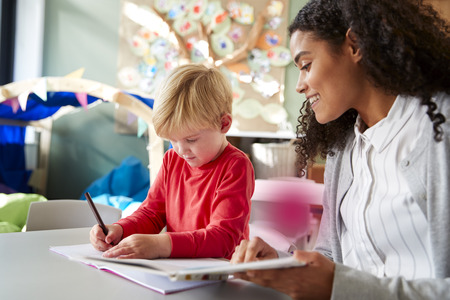Female infant school teacher working one on one with a young white schoolboy, sitting at a table in a classroom writing, close up Stock Photo