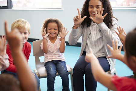 Front view of infant school children sitting on chairs in a circle in the classroom, holding up their hands and learning to count with their female teacher, close up