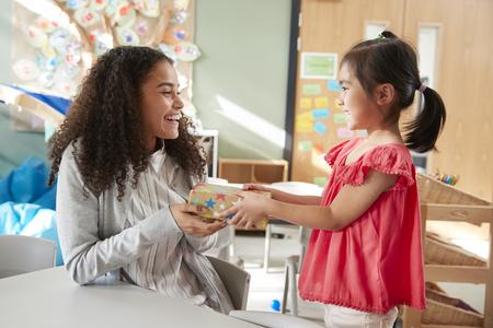 Écolière de la maternelle donnant un cadeau à son enseignante dans une salle de classe, vue latérale, gros plan