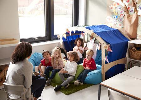 Female infant school teacher sitting on a chair showing a book to a group of children sitting on bean bags in a comfortable corner of the classroom, elevated view 版權商用圖片