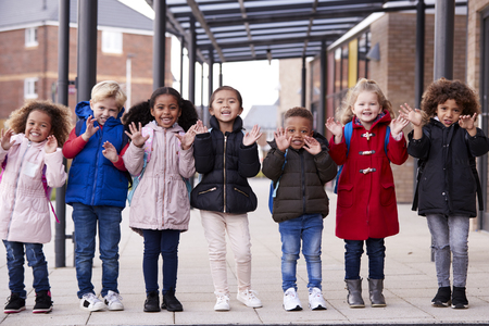 A group of smiling young multi-ethnic school kids wearing coats and carrying schoolbags standing in a row in walkway outside their infant school waving to camera, full length, front view Imagens