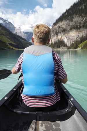 Rear View Of Man Kayaking On Beautiful Lake In Alaska