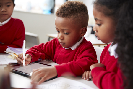 Three kindergarten school kids sitting at desk in a classroom using a tablet computer and stylus together, selective focus Imagens