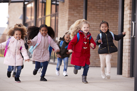 Happy young school girls wearing coats and carrying schoolbags running in a walkway with their classmates outside their infant school building