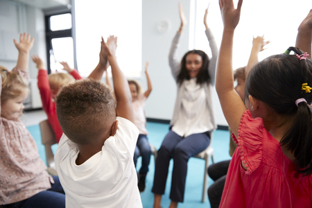 A class of infant school children sitting on chairs in a circle in the classroom, raising hands with their female teacher, close up Imagens