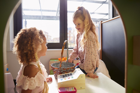 Two young schoolgirls playing shop in a playhouse at an infant school, backlit Imagens