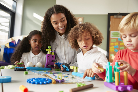 Female teacher sitting at table in play room with three kindergartne children constructing, selective focus Imagens