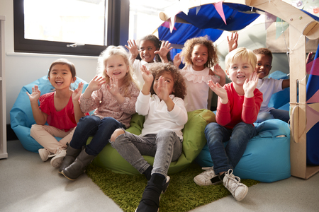 A multi-ethnic group of infant school children sitting on bean bags in a comfortable corner of the classroom, smiling and waving to camera, low angle, close up Imagens