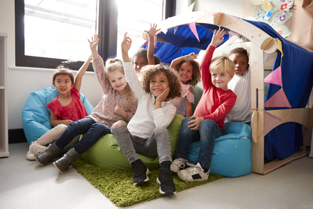 A multi-ethnic group of infant school children sitting on bean bags in a comfortable corner of the classroom, raising their hands to answer a question, low angle, close up Imagens
