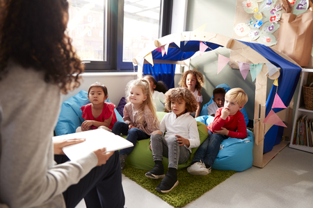 Female infant school teacher sitting on a chair reading a book to a group of children sitting on bean bags in a comfortable corner of the classroom, elevated view, close up Standard-Bild