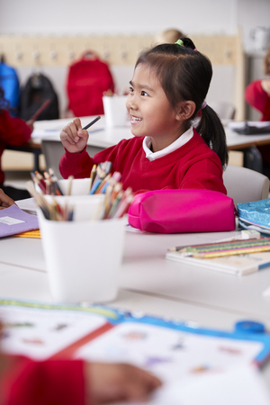 Close up of young Chinese schoolgirl wearing school uniform sitting at a desk in an infant school classroom, selective focus, vertical