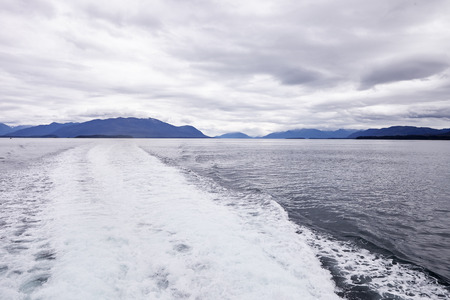 Wake Of Boat On Lake In Alaska Surrounded By Mountains And Forests