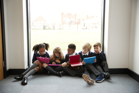 Five primary school kids sitting in a row on the floor in front of a window in a school corridor looking at tablet computers, front view, close up Banque d'images