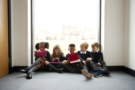Primary school kids sitting in a row on the floor in front of a window in a school corridor using tablet computers, front view