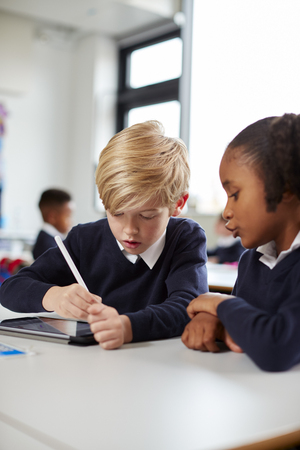 Two primary school kids using a tablet computer and stylus sitting together at desk in a classroom, vertical Stock Photo - 115388235