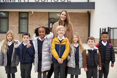Primary school kids standing in front of school with their teacher looking to camera, front view