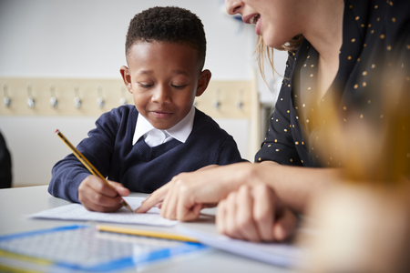 Female primary school teacher helping a young school boy sitting at table in a classroom, close up, selective focus Imagens - 115388362