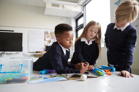 Three primary school children standing at a table in a classroom working together with toy construction blocks, close up, low angle Archivio Fotografico