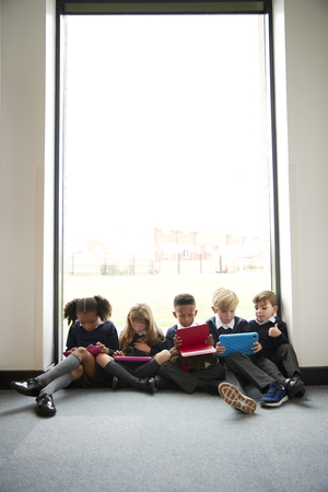 Primary school kids sitting together on the floor in front of a window in a school corridor using tablet computers, vertical Banque d'images