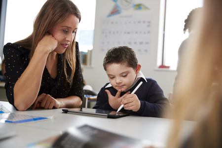 Young female teacher working with a Down syndrome schoolboy sitting at desk in a primary school classroom, selective focus Imagens