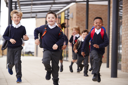 Excited primary school kids, wearing school uniforms and backpacks, running on a walkway outside their school building, front view, close up Фото со стока
