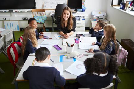 Erhöhte Ansicht einer Grundschullehrerin, die an einem Tisch sitzt und während einer Unterrichtsstunde in einem Klassenzimmer mit Schulkindern lächelt
