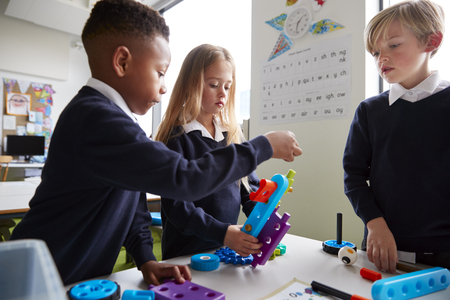 Close up of three primary school children working together with toy construction blocks in a classroom, side view