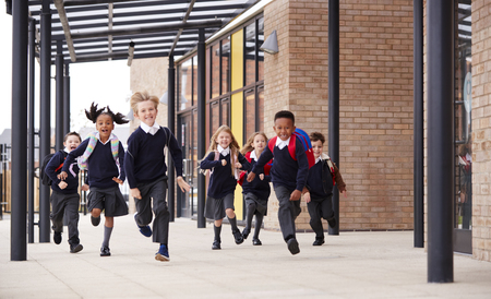Primary school kids, wearing school uniforms and backpacks, running on a walkway outside their school building, front view
