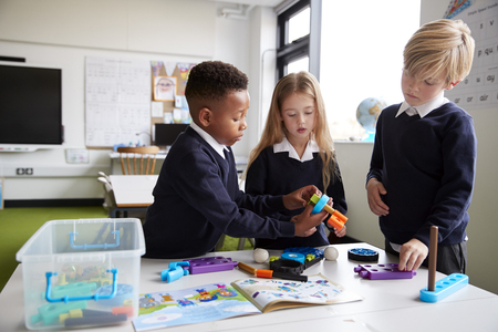 A girl and two boys standing at a table in a primary school classroom working together with toy construction blocks, close up