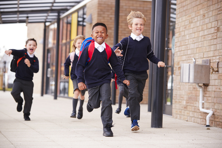 Happy primary school kids, wearing school uniforms and backpacks, running on a walkway outside their school building, front view, close up Banco de Imagens
