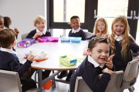 Vista in elevazione dei bambini della scuola primaria seduti insieme a una tavola rotonda per mangiare i loro pranzi al sacco, alcuni si girano per affrontare la telecamera