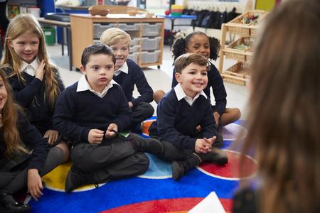 Blick über die Schulter der Lehrerin von Grundschulkindern, die vor ihr im Schneidersitz auf dem Boden des Klassenzimmers sitzen