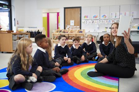 Lehrerin, die ein Buch vor ihrer Klasse von Grundschulkindern hält, die in einem Klassenzimmer auf dem Boden sitzen, Seitenansicht