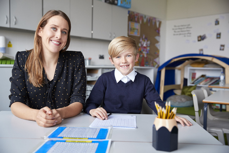 Young female primary school teacher and schoolboy sitting at a table, working one on one in a classroom, smiling to camera, front view, close up Stock Photo
