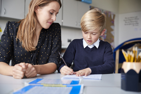 Young female primary school teacher and schoolboy sitting at a table working one on one, looking down, front view, close up