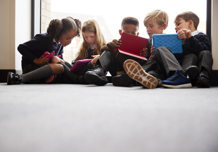 Low angle view of primary school friends sitting together in front of a window in a school corridor looking at tablet computers together